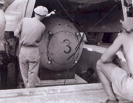"A ""Fat Man"" test unit being raised from the pit into the bomb bay of a B-29"